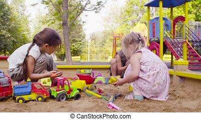 Three girls sitting in a sandbox and picking up sand - Crane...