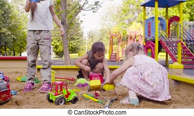 Three girls sitting in a sandbox and picking up sand - Low...