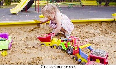 Three girls sitting in a sandbox and picking up sand - Three...