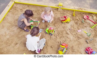 Three girls sitting in a sandbox and picking up sand - Top...