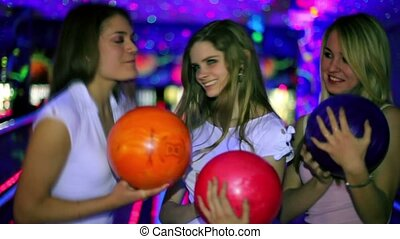 Three girls stand with bowling balls and then throw it to beat skittles