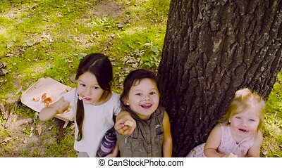 Three girls standing near the tree in the park and eating...