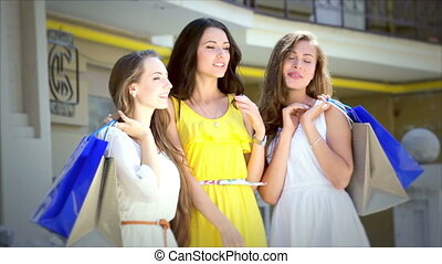 Three girls standing with shopping bags waving her friends