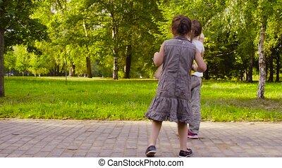 Three girls walking in the park and eating bananas at summer