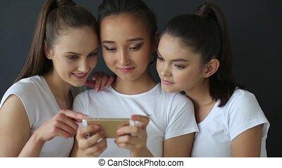 Three girls watching photos on smartphone in studio