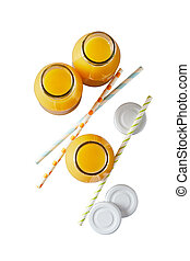Three glass bottles of freshly squeezed or liquidised orange juice viewed top down isolated on white with straws and lids