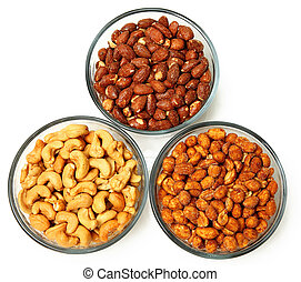 Three glass bowls filled with cashews, salted roasted almonds and honey roasted peanuts. Over white.