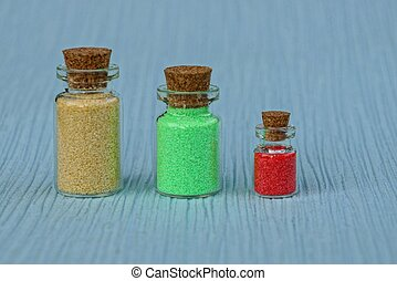three glass closed bottles with colored sand on the table