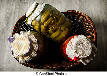 three glass jars with homemade canned vegetables lie in basket