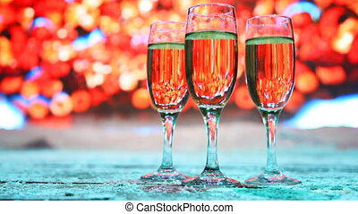 three glasses champagne or white wine stand in snow on...