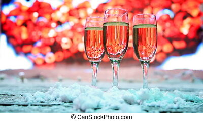 three glasses champagne or white wine stand sprinkled snow...