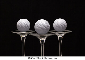 Three glasses of champagne and golf balls
