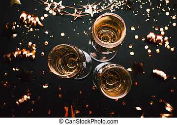 Three glasses of champagne on holiday black background with golden decoration.