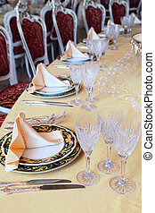Three goblets, two knives and two plates with placemat at...