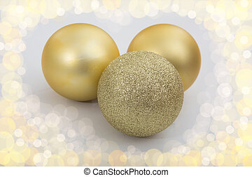 Three golden christmas balls on white background