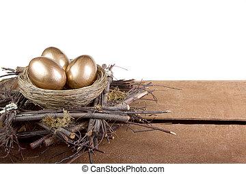A nest egg, three golden eggs in a nest, buisness concept