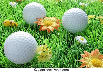 Three golf balls on artificial grass
