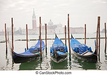 Three gondolas in Venice at the pier