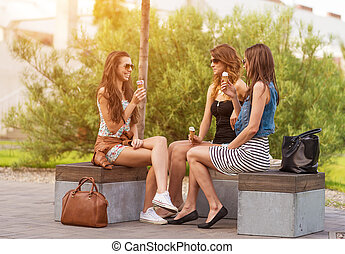 Three good girlfriends eat ice cream on a bench in the City
