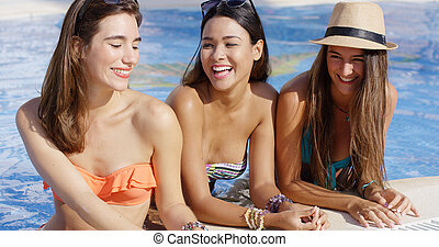 Three gorgeous friendly young women in bikinis