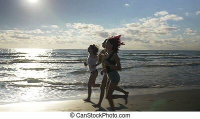 Three gorgeous women running on the beach during workout