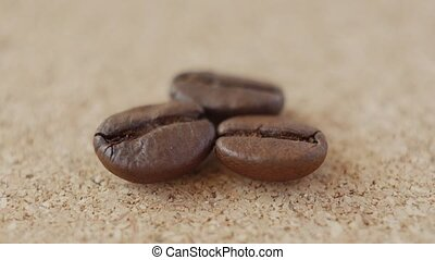 Three grains of coffee close-up on brown background.