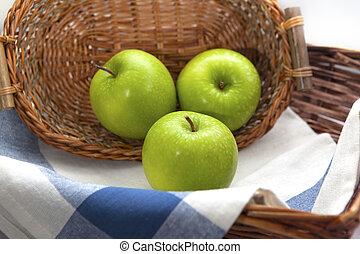 Three green apples in the brown wicker basket