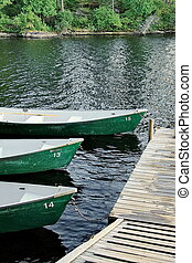 Three green boats in line tied to the dock waiting to be enjoyed.