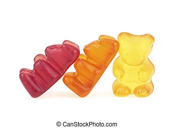 Three gummy bears on a white background. Colorful gel bear dessert.