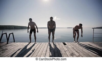 Three guys somersault their backs jumping water - Three guys...