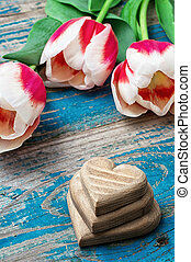 three hand-carved wooden heart with bouquet tulips