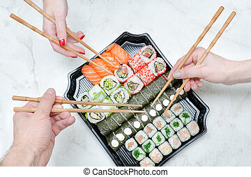 Three hands with chopsticks and sushi set. Top view