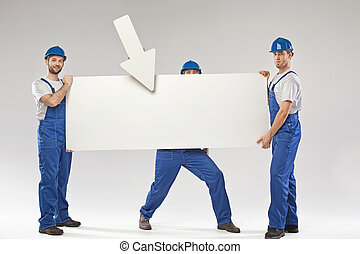 Three handsome builders holding a banner
