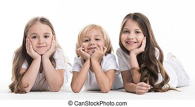 Three happy children laying on floor