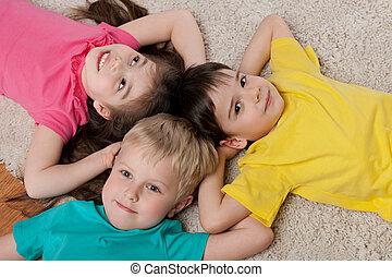 Three happy children on the white carpet