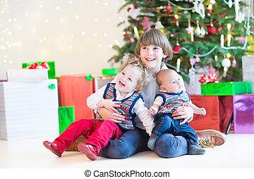 Three happy children sitting under a beautiful Christmas tree