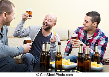 Three happy friends drinking beer