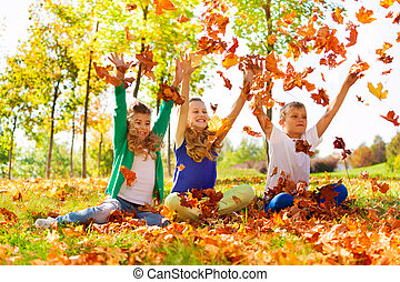 Three happy friends playing with thrown leaves in the forest...