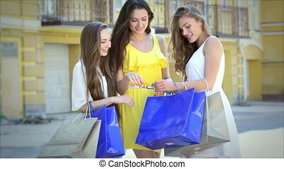 Three happy girls discuss their shopping