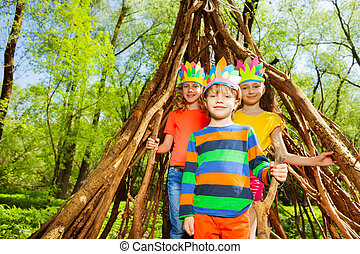 Three happy kids playing Injuns in the forest