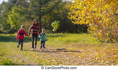 Three happy kids running together in autumn forest