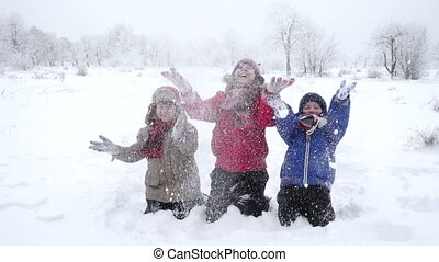 Three happy kids throwing snow on winter park, slow motion