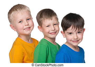 Three happy little boys are standing together against the...