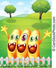 Three happy orange monster near the fence