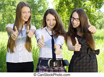 three happy student girl with thumbs-up in the park