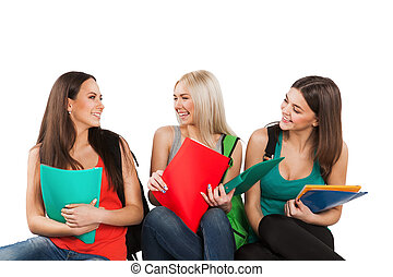 Three happy students sitting together with fun, while smiling and looking at camera isolated on white background.