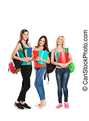 Three happy students standing together with fun, while smiling and looking at camera isolated on white background.
