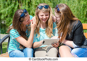 Three happy teen girl friends and tablet computer
