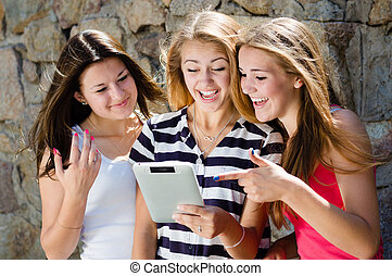 Three happy teen girl friends looking on tablet pc and laughing on summer day