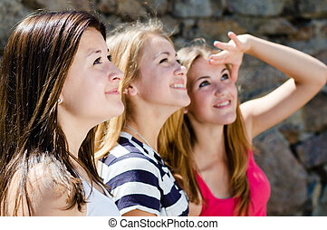 Three happy teen girl friends looking together in one direction